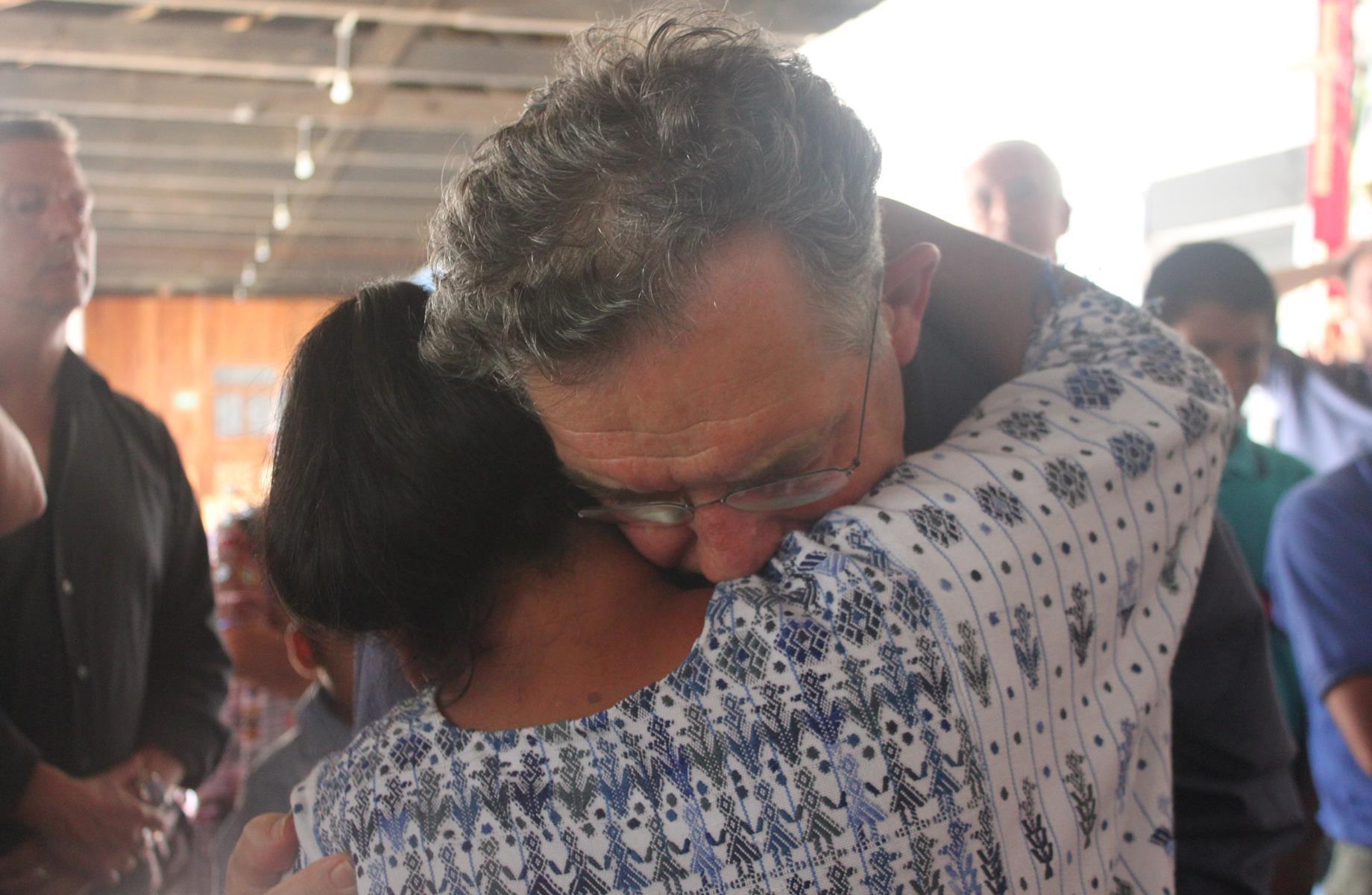 Mgr. Jousten embraces a grieving villager